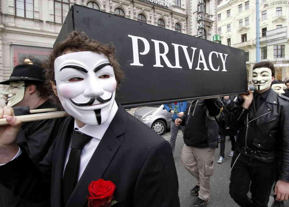 Des activistes anonymous brandissent un cercueil portant le nom de la vie privée